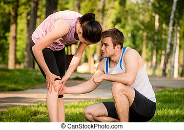 Sport - knee injured - Man helps to woman with injured knee...