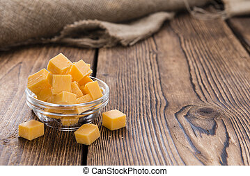 Cheddar - Pieces of Cheddar (close-up shot) on an old wooden...