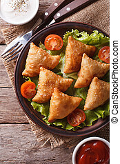 samosa on a plate with sauce closeup, vertical top view -...