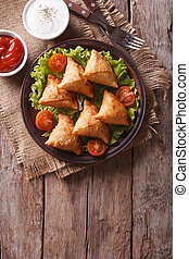 samosa on a plate with sauce on a plate , vertical top view...