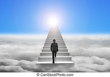 Businessman climbing the concrete stairs with blue sky...
