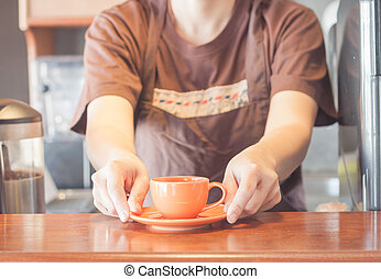 Barista offering mini orange cup of coffee, stock photo