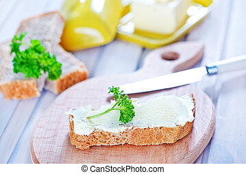bread with butter on board and on a table