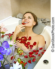 woman in rose-petals - happy beautiful woman lies in bath...