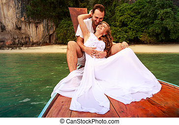 groom embrace bride sitting on longtail boat - handsome...