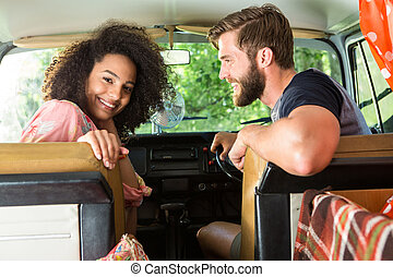 Hipster couple driving in camper van on a summers day
