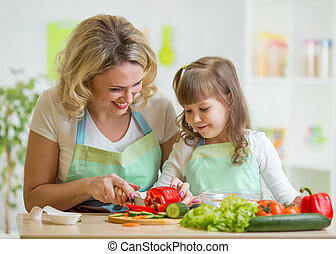 mom and her daughter preparing vegetables at kitchen -...