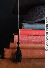 Book Steps Leading to Graduation Cap - A pile of old, used...