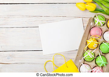 Easter background with colorful eggs and yellow tulips -...