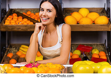 I love my job! Beautiful young woman in apron holding hand on chin and smiling while standing in grocery store with variety of fruits in the background
