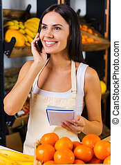 Taking order on fruits. Cheerful young woman in apron talking on mobile phone and holding note pad while standing in grocery store with variety of fruits in the background