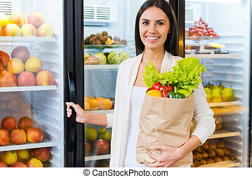 Buying the freshest products. Beautiful young woman holding shopping bag with fruits and smiling while standing in grocery store near refrigerator