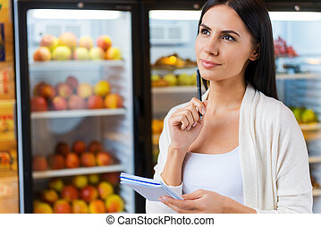 Woman with shopping list Thoughtful young woman holding...