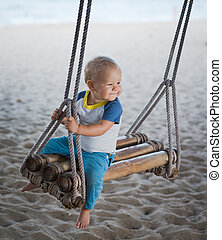 Baby on a swing - Baby sitting on a bamboo swing