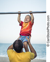 Baby hanging - Father helps baby hanging on a pull-up bar