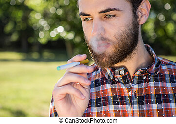 Hipster smoking an electronic cigarette on a summers day