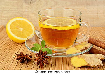 Ginger tea-ingwertee on wooden mat with lemon,cinnamon,anise...