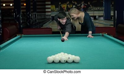 Happy couple playing pool she supports her partner The...