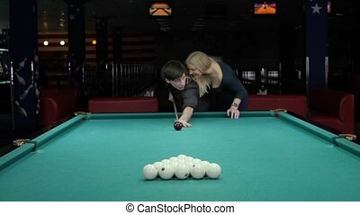 Young couple playing pool in entertainment center. Slow motion