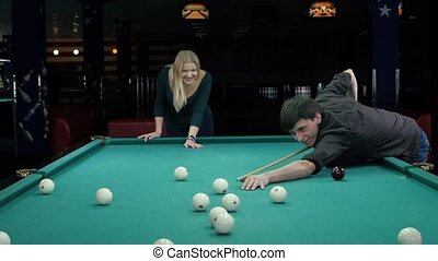 Young couple playing pool in a bar. Slow motion - Young...