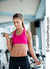 lifting some weights and working on her biceps in a gym -...