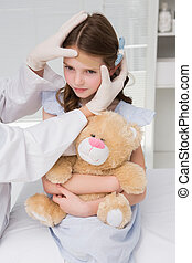 Doctor making plaster in little girl in medical office