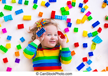 Little girl playing with toy blocks - Cute funny preschooler...