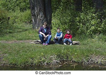 Spring on the shores of mother with children sitting on a...