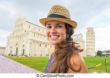 Portrait of happy young woman with map on piazza dei...