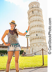 Funny young woman supporting leaning tower of pisa, tuscany,...