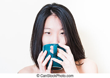 Young asian woman closeup drinking from blue-green cup -...