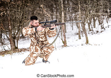 Professional hunter with sniper rifle aiming and shooting during winter