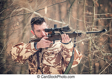 Man holding a sniper and shooting on an open season, looking...