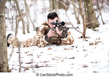 Hunter shooting with a sniper rifle, aiming and firing bullets