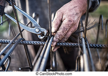 Details of construction worker - hands securing steel bars...