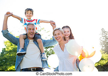 Happy family walking at the park on a sunny day