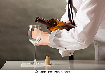 Man waiter pouring wine into glass - Male waiter or butler...