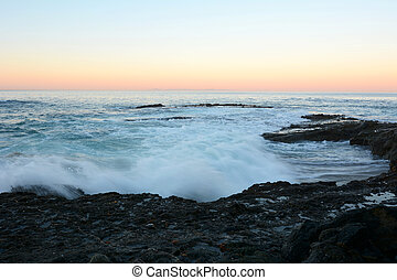 Wave and reef at beach - A wave moves into shore and