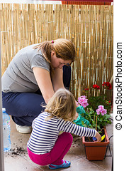 Planting Flowers - Mother and daughter together Planting...