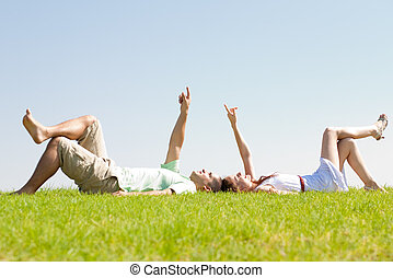 couple lie down on grass - young couple lie down on grass...