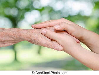 Young woman holding her grandmother hand