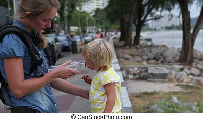 little blonde child drinks water from plastic bottle stand...