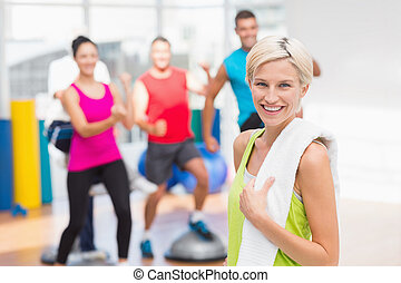 Portrait of happy woman holding towel at gym - Portrait of...