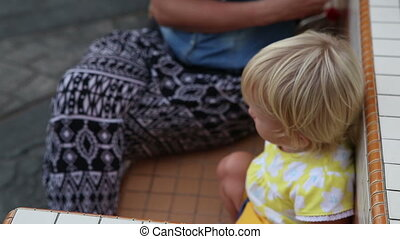 blonde child sits by mother on bench