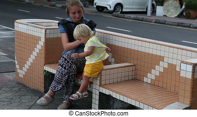 blonde child plays with mother on bench near road - little...