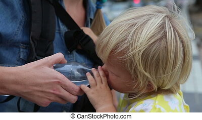 closeup little blonde child drinks water from plastic bottle...