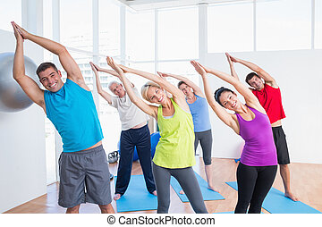 Happy people doing stretching exercise in yoga class -...