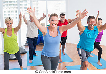 People exercising in gym class - Happy fit men and women...