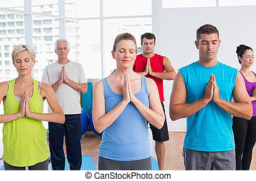 People meditating with hands joined in fitness club - Fit...
