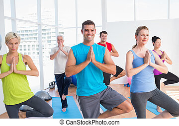 People practicing tree pose in fitness studio - Happy men...